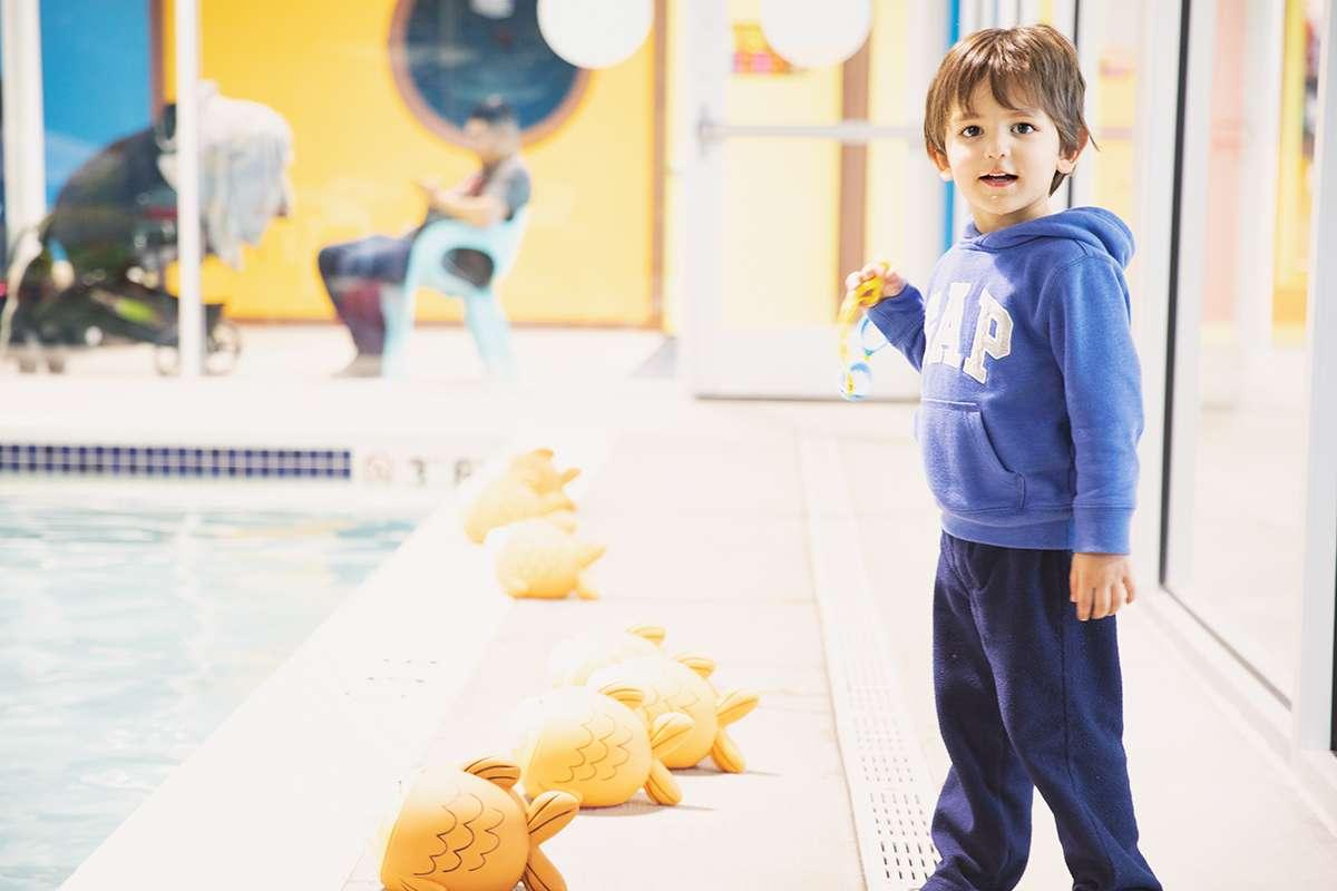 goldfish swim school kid standing beside pool
